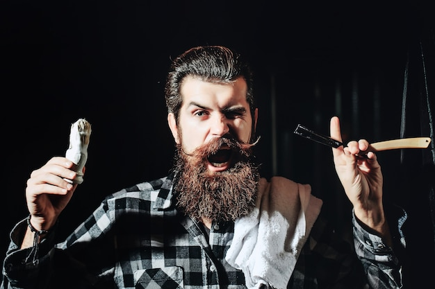 Excired barbiere uomo barbuto nel negozio di barbiere forbici da barbiere e rasoio da barbiere vestito vintage negozio di barbiere rasatura ritratto uomo barbuto baffi uomini brutale ragazzo forbici rasoio