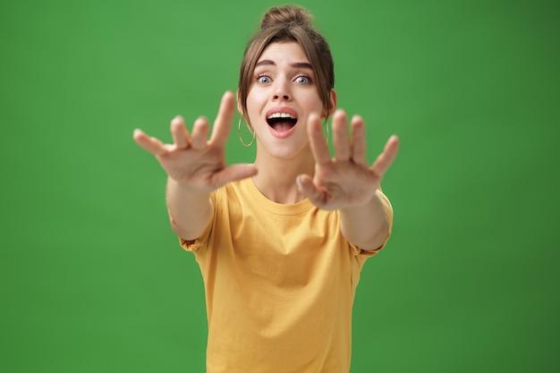 Giovane donna eccitata e dipendente dall'aspetto goog che allunga le mani davanti alla telecamera con uno sguardo spericolato che vuole afferrare qualcosa che desidera vedere cosa desiderava da molto tempo oltre il muro verde.