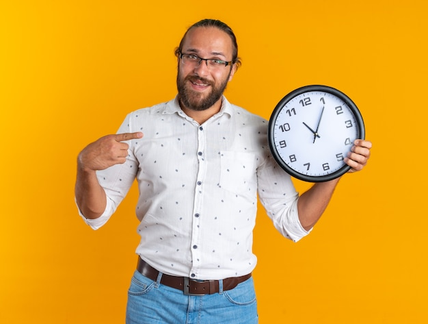 Eccitato adulto bell'uomo con gli occhiali che mostra e indica l'orologio guardando la telecamera isolata sul muro arancione