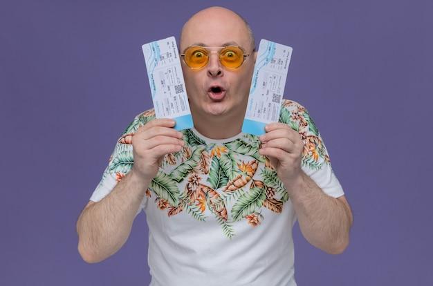 Uomo adulto eccitato con occhiali da sole in possesso di biglietti aerei
