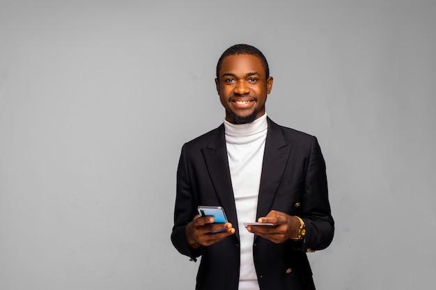 Eccitato ragazzo afroamericano sta usando uno smartphone e una carta di credito per fare acquisti online, un uomo di colore felice sta ordinando cibo online, un maschio che paga per l'acquisto tanto atteso sul telefono cellulare. e-banking