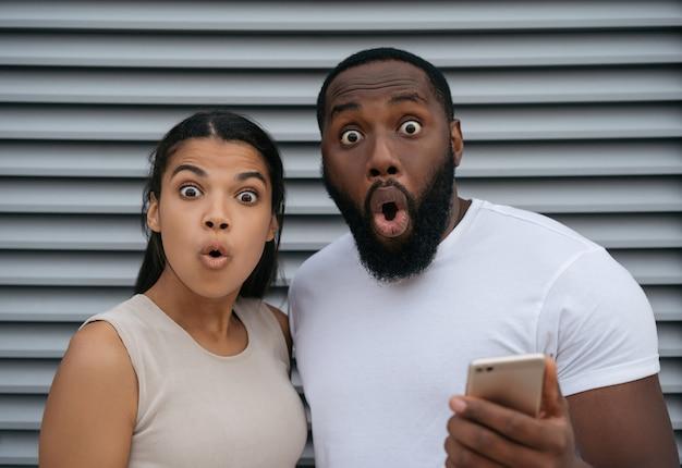Uomo afroamericano emozionante e donna che tengono il telefono cellulare, acquisti in linea