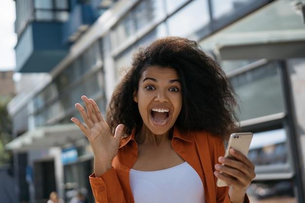 Smartphone emozionante della tenuta della donna dell'afroamericano, acquistante in linea