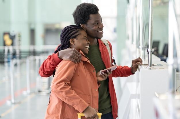 La coppia africana emozionante viaggia dopo i viaggiatori covid pandemici in aeroporto al check-in felici di viaggio Foto Premium