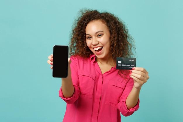 La ragazza africana emozionante in vestiti casuali tiene il telefono cellulare con lo schermo vuoto in bianco, carta bancaria di credito isolata su fondo blu del turchese. concetto di stile di vita di emozioni sincere della gente. mock up copia spazio.