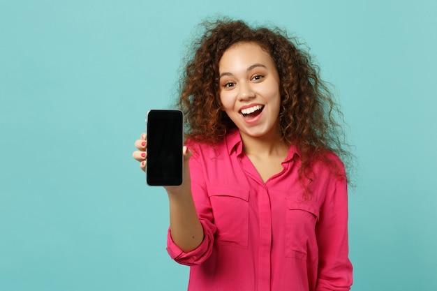 La ragazza africana emozionante in vestiti casuali tiene il telefono cellulare con lo schermo vuoto in bianco isolato sul fondo blu della parete del turchese in studio. persone sincere emozioni, concetto di stile di vita. mock up copia spazio.
