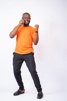 L'uomo africano eccitato che fa una telefonata festeggia, in piedi su uno sfondo bianco