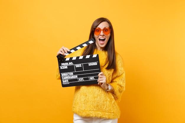 Eccitata giovane donna stupita in maglione di pelliccia, occhiali da vista a cuore arancione che tengono il classico ciak nero per la produzione di film isolato su sfondo giallo. persone sincere emozioni, stile di vita. zona pubblicità.