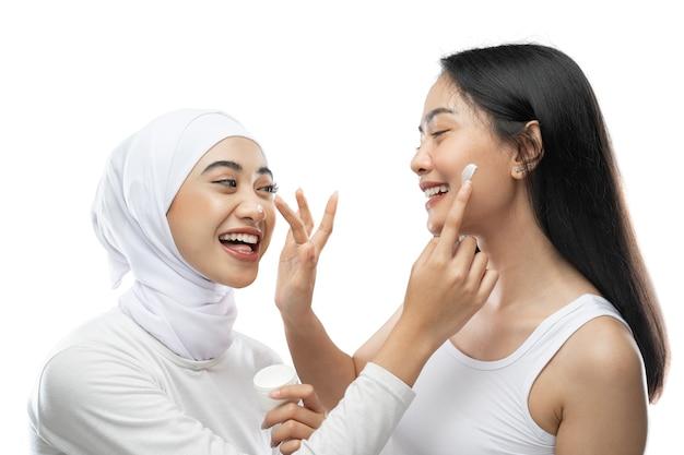 Eccitato migliore amico asiatico che applica la crema per il viso con le dita delle mani