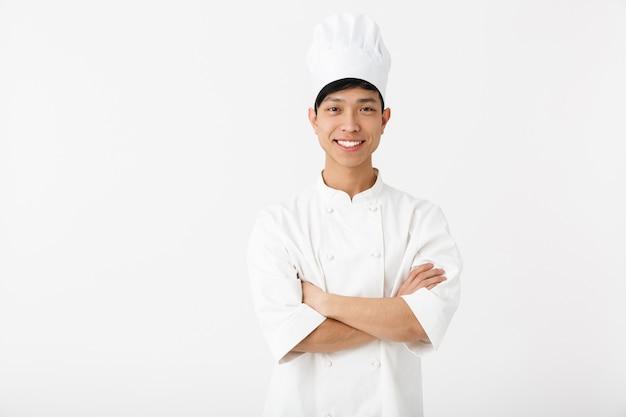 Cuoco unico asiatico emozionante che indossa la condizione uniforme isolata sopra la parete bianca, gesticolando
