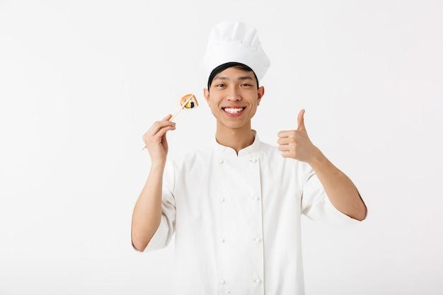 Cuoco unico asiatico emozionante che indossa la condizione uniforme isolata sopra la parete bianca, preparante i sushi