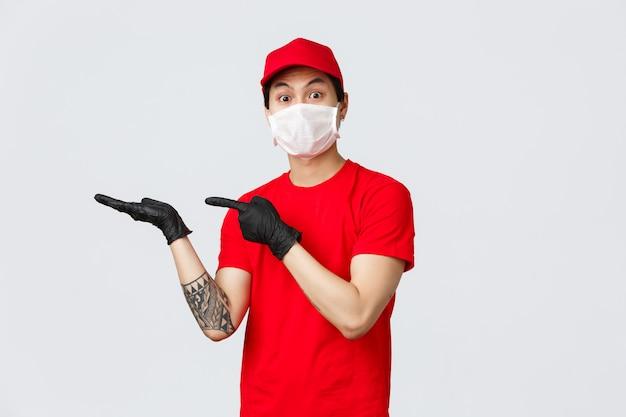 Eccitato uomo asiatico consegna in berretto rosso, t-shirt, indossando guanti protettivi in lattice e mascherina medica