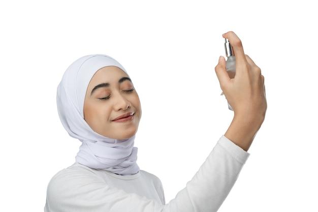 Eccitata donna asiatica hijab che indossa un abito bianco schizza una bottiglia di siero per la cura del viso