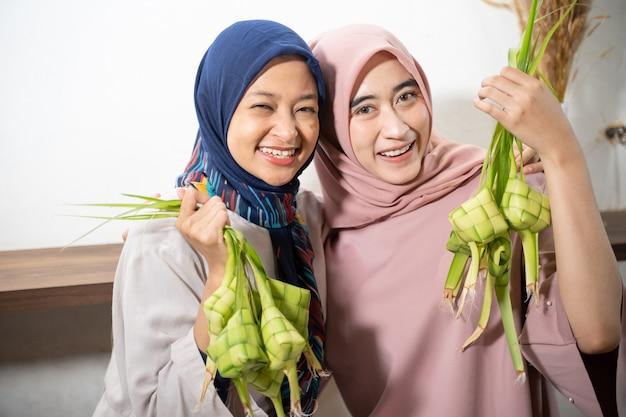 Eccitata donna musulmana asiatica che produce riso ketupat con foglia di cocco durante il ramadan kareem preparando per la celebrazione di eid fitri mubarak