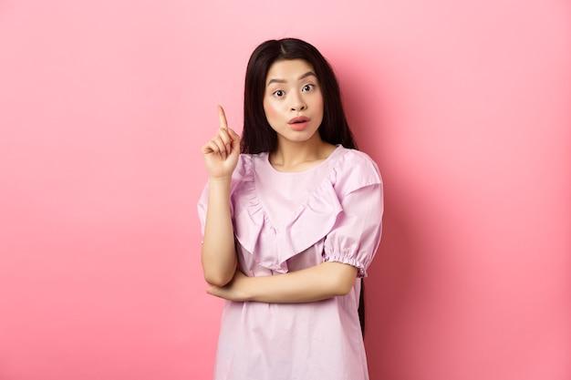 Eccitata donna asiatica che lancia un'idea, alzando il dito nel segno di eureka, ha un piano o una soluzione, in piedi su sfondo rosa.