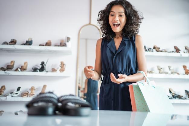 Acquisto asiatico emozionante della donna che esamina le scarpe