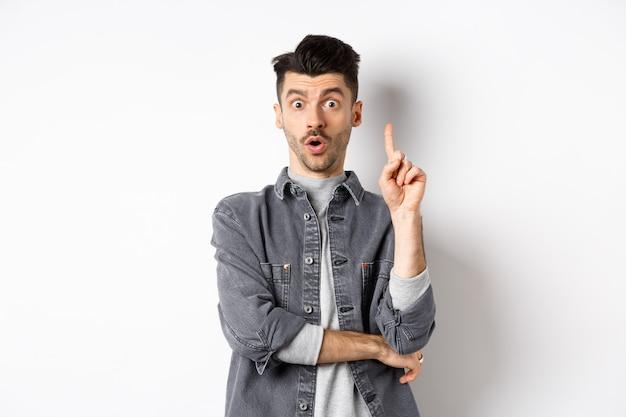 Ragazzo barbuto eccitato che lancia un'idea, alza il dito in un gesto eureka e dice suggerimento, ha un piano, in piedi su sfondo bianco.