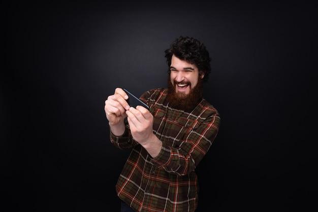 Ragazzo barbuto eccitato che gioca sul cellulare su sfondo scuro del muro