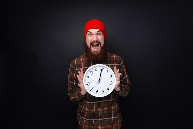Eccitato ragazzo barbuto con cappello rosso, con in mano un orologio in piedi su uno sfondo scuro del muro