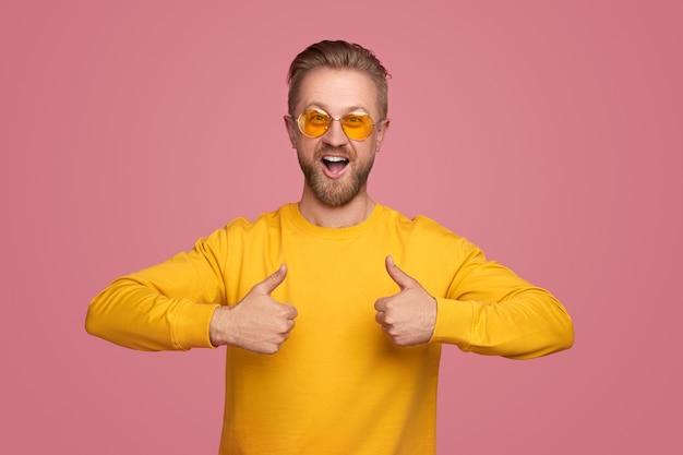 Eccitato ragazzo barbuto in felpa gialla e occhiali da sole alla moda che mostrano il pollice in alto gesto su sfondo rosa
