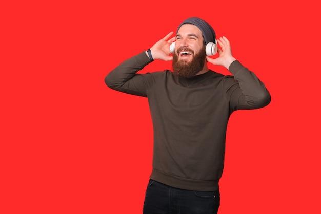L'uomo barbuto eccitato sta godendo la musica in cuffia.