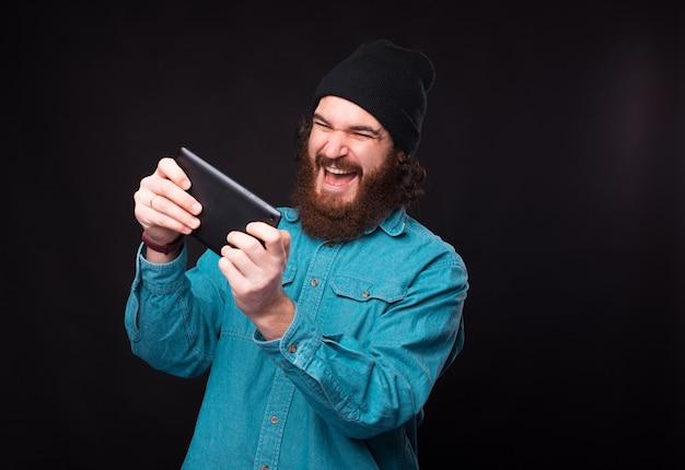 Eccitato uomo barbuto sta giocando in auto sul suo tablet su sfondo nero.