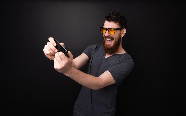 Uomo barbuto eccitato che gioca su smartphone su sfondo grigio scuro