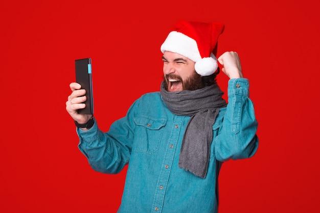 Il vincitore barbuto eccitato che indossa il cappello di natale sta guardando il suo tablet mentre gesticola