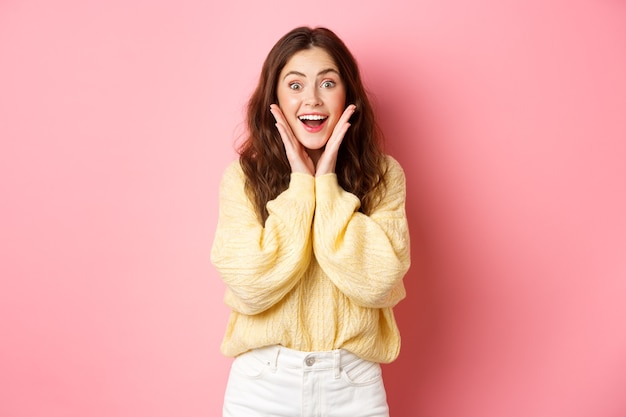 Bella ragazza emozionante che fissa sorpresa e stupita, tenendosi per mano sulle guance e ansimante, guardando con la faccia stupita all'offerta promozionale, in piedi vicino alla parete rosa dello spazio della copia.