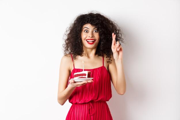 Ragazza di compleanno eccitata in vestito rosso, dita incrociate mentre esprime il desiderio e soffiando la candela sulla torta di compleanno, sorridendo felice, sfondo bianco.