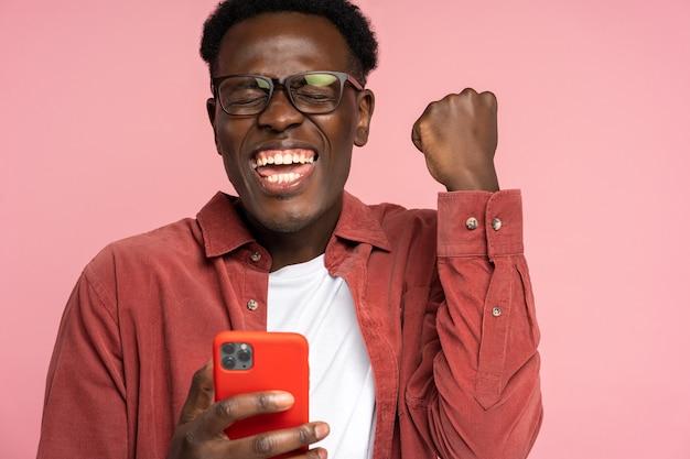 Eccitato uomo nero millenario tenere il telefono cellulare, facendo il gesto del vincitore sul rosa