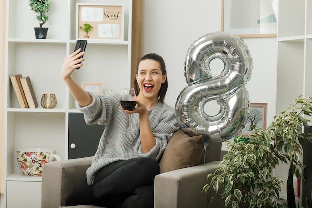 Eccitata bella ragazza sbattuta le palpebre durante la felice giornata delle donne con in mano un bicchiere di vino, si fa un selfie seduto sulla poltrona in soggiorno