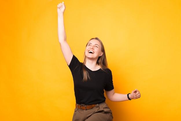 La donna bionda emozionante sta celebrando la vittoria. ritratto su sfondo giallo.