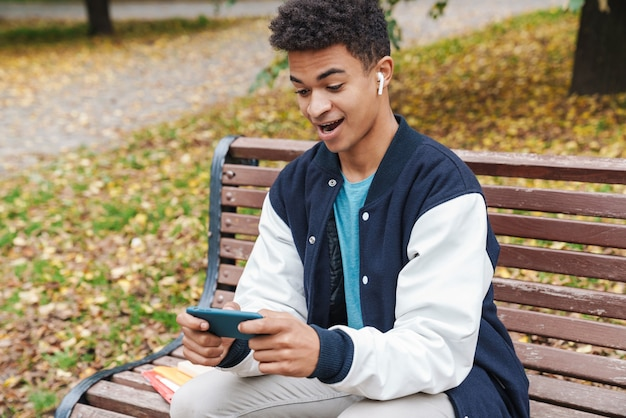 Eccitato ragazzo studente seduto su una panchina al parco, giocando con il cellulare