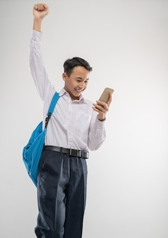 Un ragazzo eccitato indossa un'uniforme scolastica usando un telefono mentre alza la mano e porta uno zaino