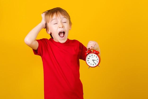 Ragazzo eccitato con orologio. sbrigati. sveglia scioccata della tenuta del bambino, sopra giallo. ragazzino urlando. Foto Premium