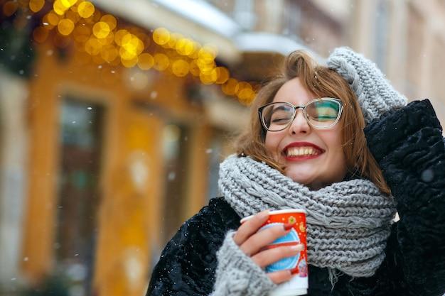 Eccitata donna bruna indossa sciarpa lavorata a maglia e occhiali beve caffè in strada durante la nevicata. spazio vuoto