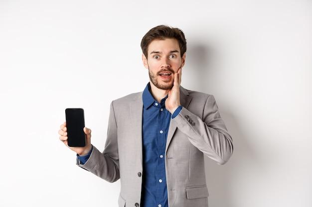 Uomo d'affari eccitato in vestito che mostra lo schermo vuoto dello smartphone e ansimante stupito, dimostra l'applicazione, in piedi su sfondo bianco.