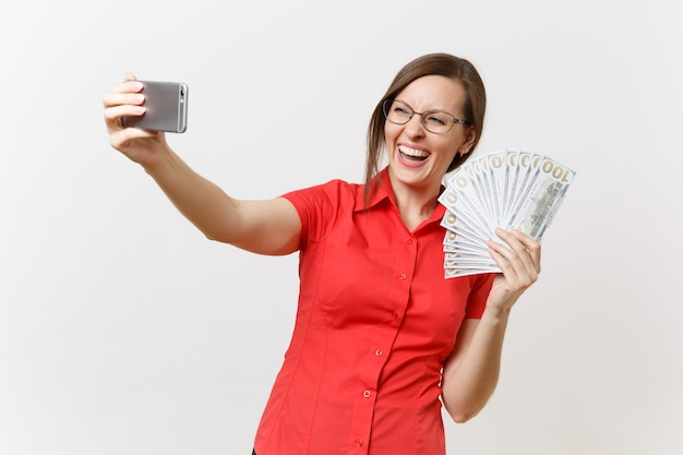 Donna d'affari eccitata in camicia rossa che fa scattare selfie sul telefono cellulare con un sacco di dollari, denaro contante isolato su sfondo bianco. insegnamento dell'istruzione nel concetto di università delle scuole superiori.