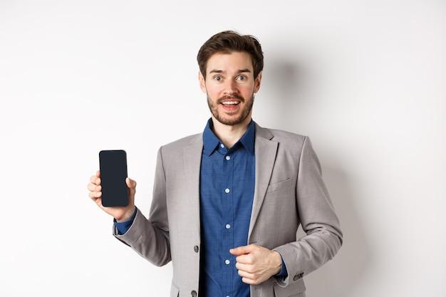 Amministratore delegato eccitato dell'uomo d'affari in vestito che mostra lo schermo del telefono vuoto e sorridente, promo online di pubblicità, in piedi su sfondo bianco