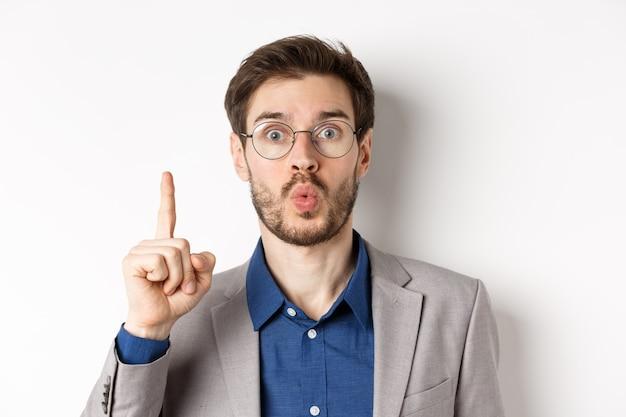 Uomo d'affari eccitato in bicchieri e idea di lancio del vestito, alzando il dito e dire suggerimento, hanno un piano, in piedi su sfondo bianco.