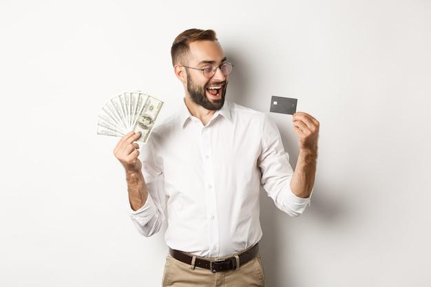 Uomo d'affari eccitato che tiene soldi e guarda la carta di credito, in piedi su sfondo bianco