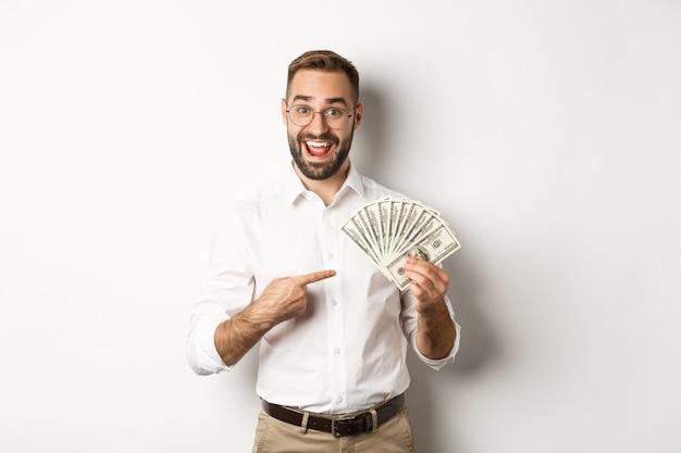 Uomo d'affari eccitato che punta al denaro, mostra dollari e sorride, in piedi su sfondo bianco