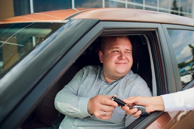 Uomo d'affari emozionante sitting in car che mostra la nuova chiave dell'automobile
