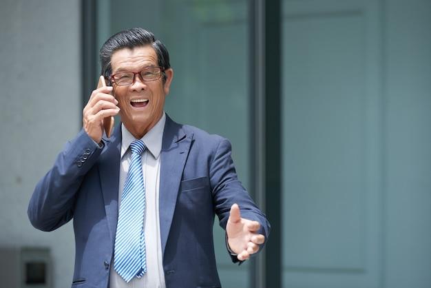 Uomo d'affari eccitato che parla al telefono