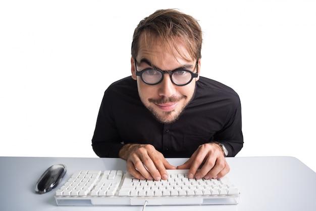 Uomo d'affari emozionante che per mezzo del computer e con gli occhiali