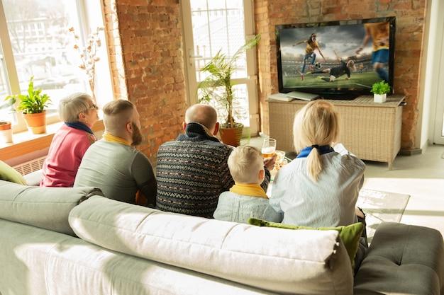 Famiglia caucasica eccitata che guarda la partita sportiva del campionato di calcio femminile a casa