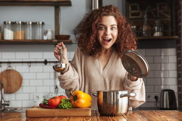 Eccitata donna caucasica che tiene in mano un mestolo da cucina mentre mangia una zuppa con verdure fresche in cucina a casa