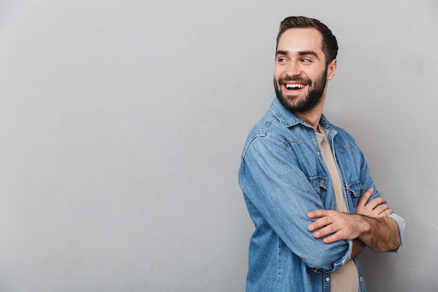 Eccitato uomo allegro che indossa camicia isolata sopra il muro grigio, braccia conserte, guardando lontano