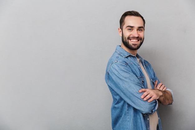 Eccitato uomo allegro che indossa camicia isolato su muro grigio, braccia conserte